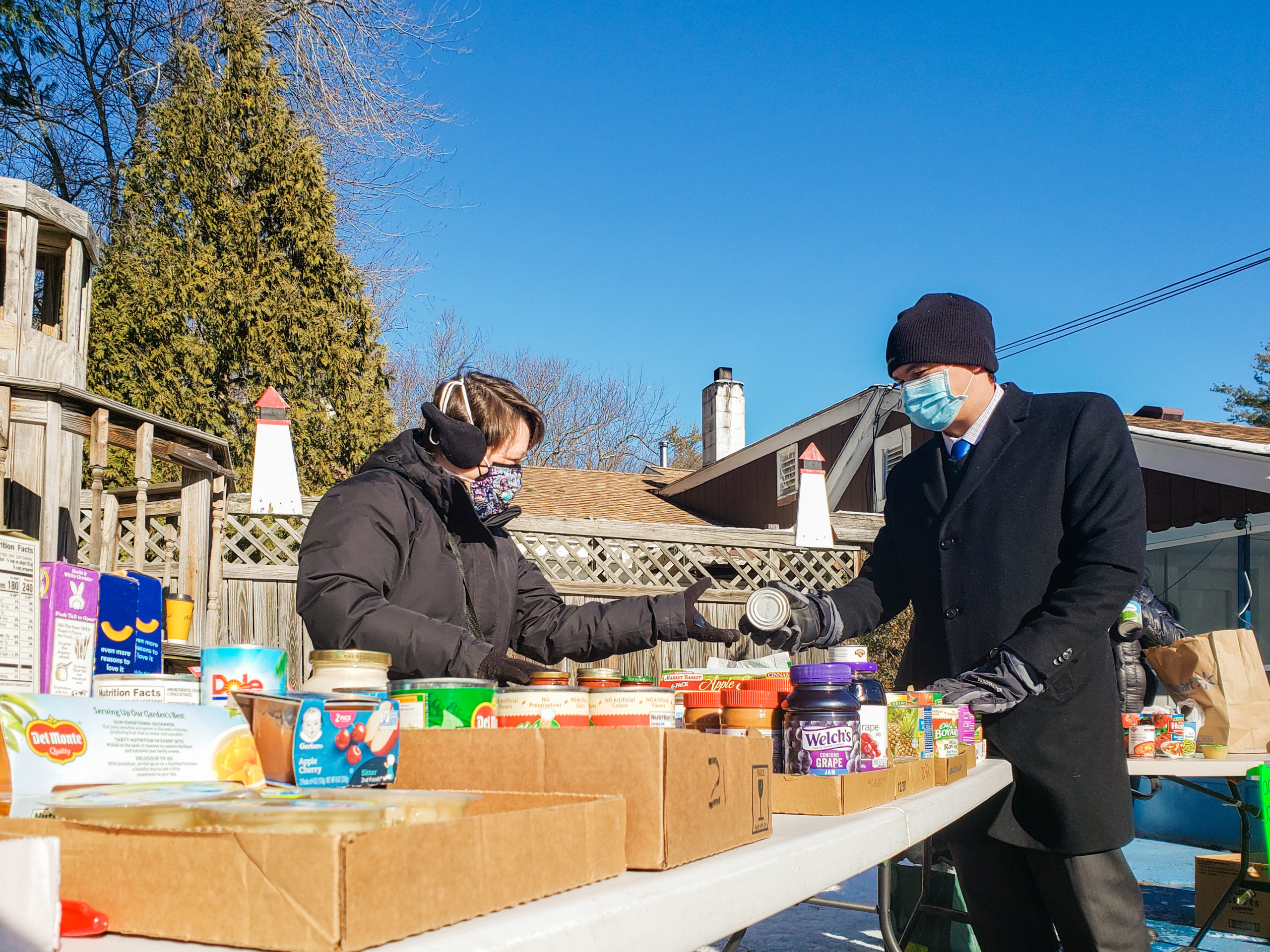 Rep. Sena hands Carrie Ayers of the Lunenburg DTC a can of food at a Lunenburg DTC and Lunenburg Turkey Hill Family Lions Club food drive